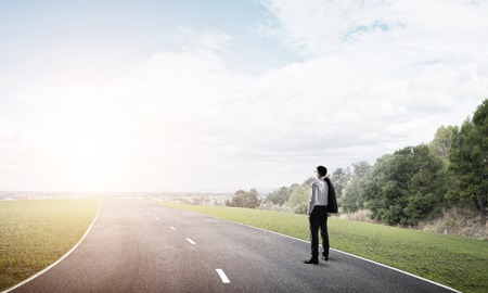 looking ahead: Elegant businessman on road standing with back and looking ahead Stock Photo