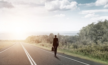 looking ahead: Elegant businesswoman on road standing with back and looking ahead