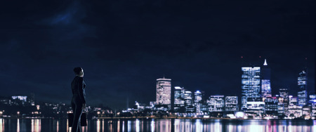 corporate buildings: Businesswoman standing with back against night city panoramic view