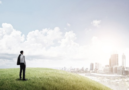to observer: Businessman standing with back on top of hill and viewing modern city