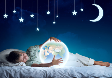 glowing earth: Cute boy in bed looking at glowing Earth planet. Stock Photo