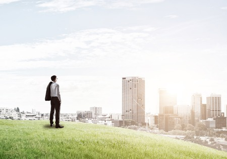 marketanalyze: Businessman standing with back on top of hill and viewing modern city