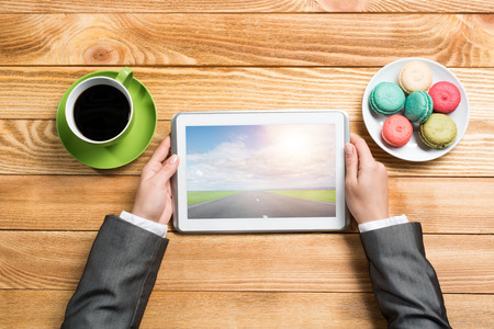communicator: Top view of businesswoman sitting at wooden table and using tablet pc