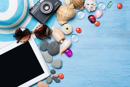 Straw hat sunglasses and photocamera among sea shells and stones on wooden surface Stock Photo