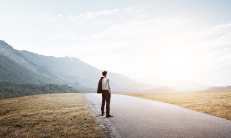 challenges ahead: Elegant businessman on road standing with back and looking ahead Stock Photo