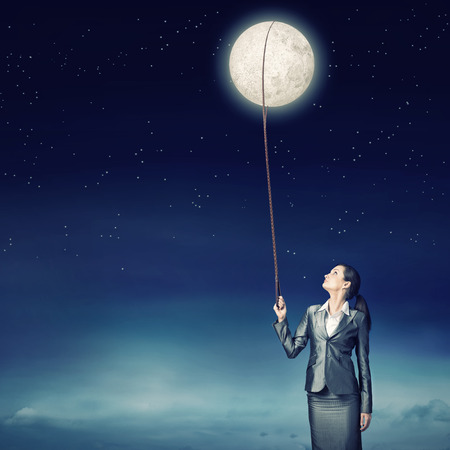 Young woman in suit holding moon planet on lead Stock Photo