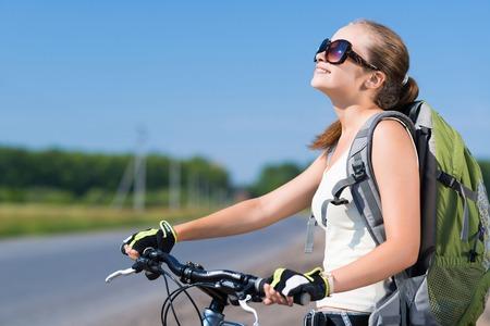 adolescencia: Mujer bonita joven con la bicicleta montar mochila al aire libre