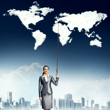 Businesswoman in suit holding world map on lead