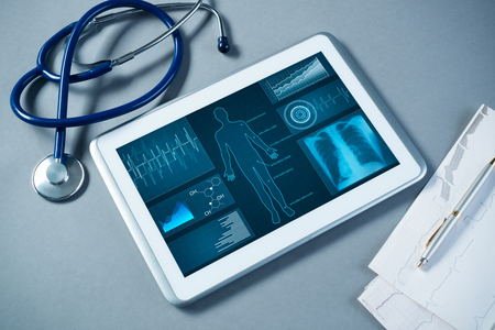 White tablet pc and doctor tools on gray surface Stock Photo