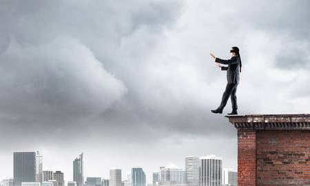 unknown men: Businessman with blindfolder on eyes walking on building top