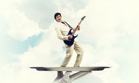 Businessman on metal tray playing electric guitar against blue sky background Stock Photo