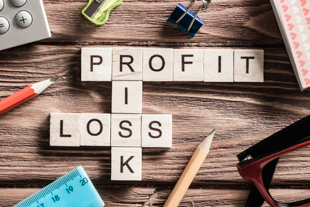 perdidas y ganancias: Profit loss and risk words on workplace collected of wooden cubes
