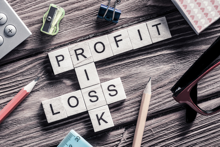 perdidas y ganancias: Profit loss and risk words on workplace collected of wooden cube