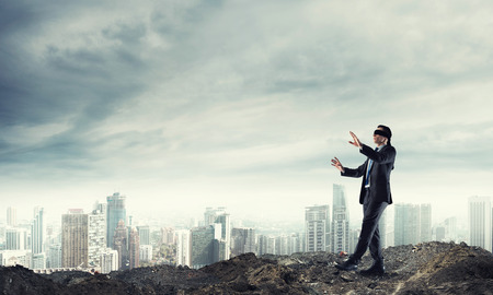 Young businessman in blindfold walking carefully and cityscape at background