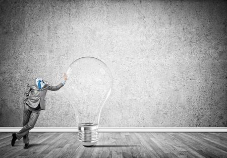 careerist: Headless businessman in empty room leaning on glass light bulb