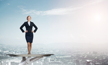 Confident elegant businesswoman presented on metal tray against cityscape background Stock Photo