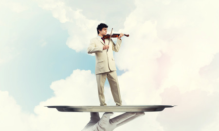 Businessman on metal tray playing violin against blue sky background Stock Photo