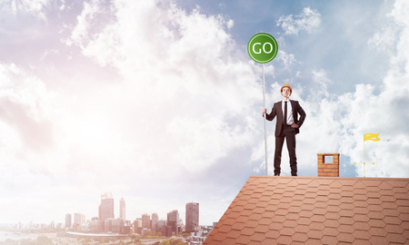 Businessman in suit on house top with ecology concept signboard. Mixed media Stock Photo