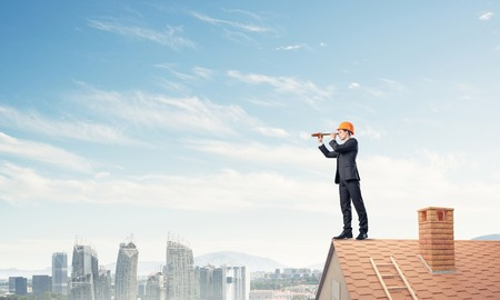suburbian: Engineer man standing on roof and looking in spyglass. Stock Photo