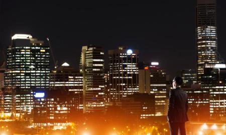 Businessman viewing night glowing city Stock Photo