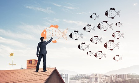 Businessman standing with back on house brick roof and drawing.