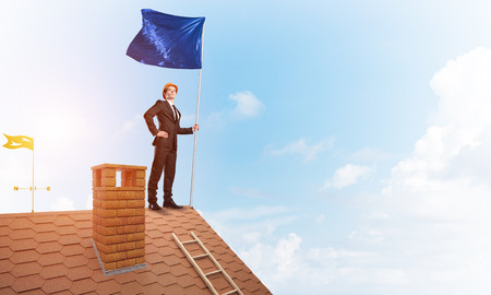 Young businessman with flag presenting concept of leadership. Mixed media Stock Photo