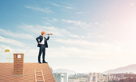 suburbian: Engineer man standing on roof and looking in spyglass. Mixed med Stock Photo