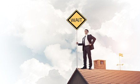 Young businessman on house brick roof holding yellow signboard.