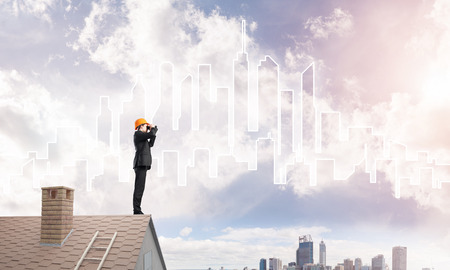 suburbian: Engineer man standing on roof and looking in binoculars. Stock Photo