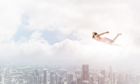 weightlessness: Young woman flying high in blue sky