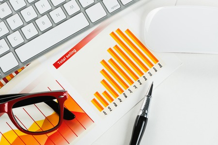 Business workplace with keyboard glasses and financial documents on table Stock Photo