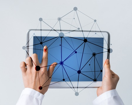 Tablet pc device with connection lines on screen in hands of doctor Stock Photo