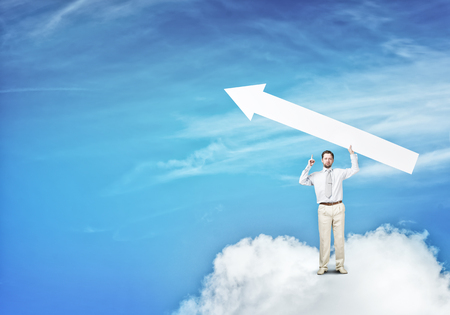 Handsome businessman standing on cloud holding white arrow