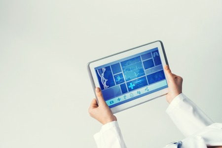 electronic tablet: Tablet pc device with medicine interface screen in hands of doctor