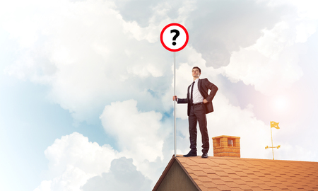 Young businessman with roadsign on roof edge. Mixed media Stock Photo