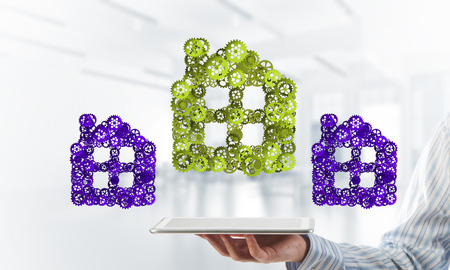 Close of businessman holding tablet pc with house sign made of connected gears. Mixed media Stock Photo