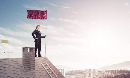 real leader: Businessman standing on house roof and red holding flag. Mixed media