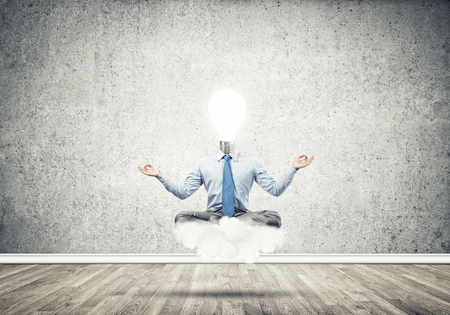Businessman sitting in lotus pose and light bulb instead of his head Stock Photo