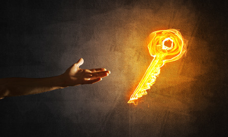Close of man hand showing on fire glowing key symbol 版權商用圖片
