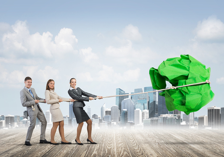 big ball: Office employees pulling together big crumpled paper ball Stock Photo
