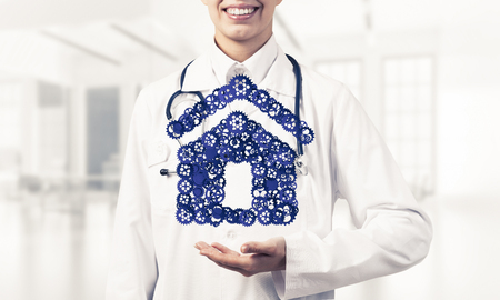 Hand of woman doctor showing house or home gear sign in palm