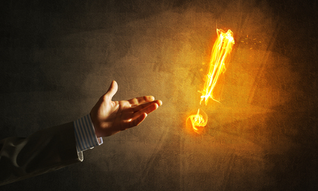 Businessman hand and fire glowing exclamation mark