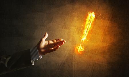 Main d'homme d'affaire et feu, point d'exclamation brillant