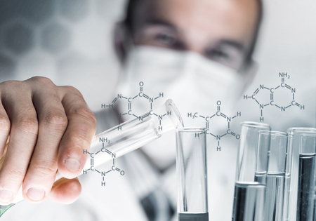 Young scientist mixing reagents in glass flask in clinical laboratory Stock Photo