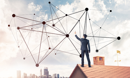 Young man standing with back on roof and drawing connection lines. Mixed media Stock Photo