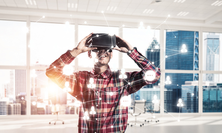 modified: Young man with virtual reality headset or 3d glasses over connection background . Mixed media