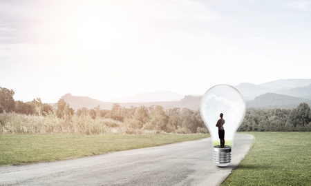trapped: Young businesswoman trapped inside of light bulb on countryside road
