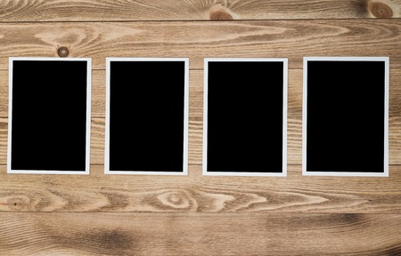 old photograph: Blank photo frame hanging on rope on wooden textured background