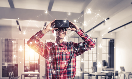 mixed media: Young man with virtual reality headset or 3d glasses over connection background . Mixed media