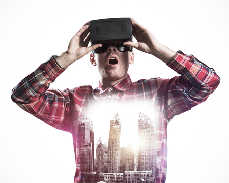 double game: Young man with virtual reality headset or 3d glasses over cityscape background